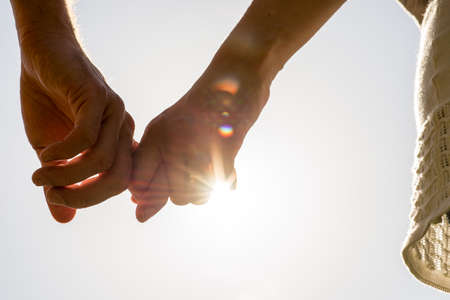 Photo for Close up Hands of Romantic Couple Holding Together with Sun Rays on a White Sky. - Royalty Free Image