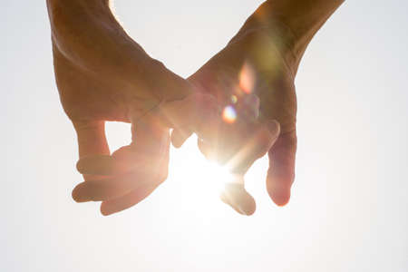 Photo pour Couple holding hands towards the sun with bright sun flare between the silhouetted fingers on a pale blue sky, close up view in a conceptual image. - image libre de droit