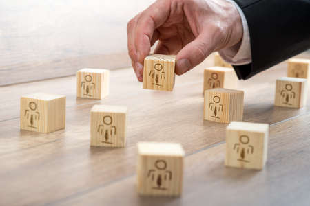 Foto de Customer-Managed Relationship Concept - Businessman Arranging Small Wooden Blocks with Symbols on the Table. - Imagen libre de derechos