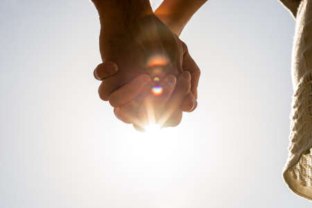 Photo pour Clasped hands of a young romantic man and woman against a bright sun flare with copyspace, conceptual image of love and friendship. - image libre de droit