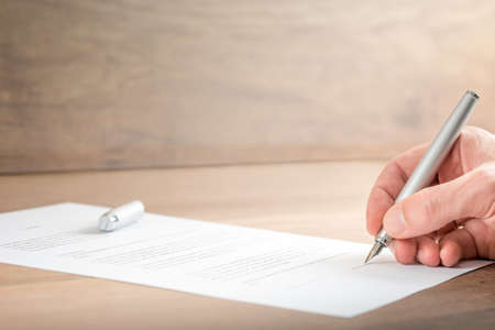 Photo pour Close up Hand of a Businessman Signing a Contract Document on Top of a Wooden Table. - image libre de droit