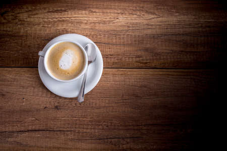 Foto de Top view of a delicious Cup of freshly brewed aromatic cappuccino standing on a wooden table. - Imagen libre de derechos