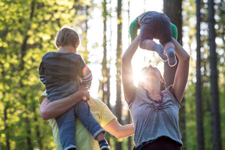 Foto de Parents playing with their two young children outdoors in a green spring forest backlit by a glowing sun as they enjoy the tranquility of nature. - Imagen libre de derechos