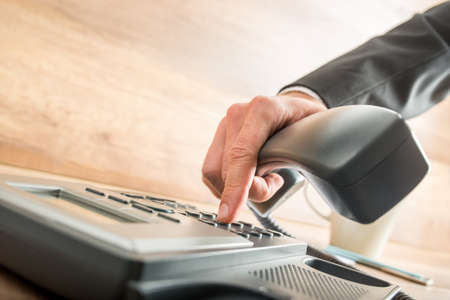 Foto de Consultant holding the receiver of a corded desk phone while dialing, in the office. - Imagen libre de derechos