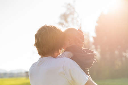 Photo pour Loving protective father cradling his young baby in his arms in the warm glow of the sunlight. - image libre de droit