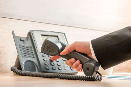 Photo pour Closeup of a hand in a formal elegant suit dialing a telephone number on a classical black landline phone. Conceptual of global business communication and telemarketing. - image libre de droit