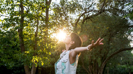 Photo pour Woman meditating in nature standing with outspread arms as the rising sun touches her face in a woodland setting , upper body in profile. - image libre de droit