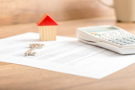 Photo pour Silver house key lying on a contract for house sale, lease, insurance or mortgage in a real estate concept, viewed low angle with focus to the tip. - image libre de droit