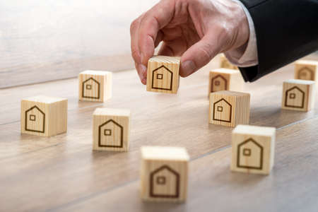 Foto de Businessman Hand Arranging Small Wooden Cubes with House Drawings on Top of the Table for Realty Concept. - Imagen libre de derechos