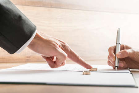 Photo pour Male hand pushing a wedding ring over to a female hand about to sign  divorce papers. Conceptual of divorce or marriage. - image libre de droit