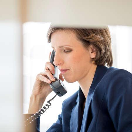 Foto de View through an internal office partition of a successful young businesswoman sitting at her desk making a phone call on a landline telephone, profile view. - Imagen libre de derechos