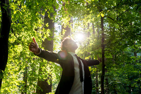 Photo for Businessman standing with his arms outspread showing thumbs up sign celebrating business success in woodland with fresh green leaves on the trees backlit by the rays of the sun, low angle view. - Royalty Free Image