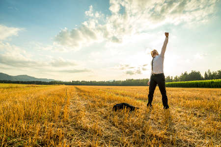 Foto de Young Businessman Standing in the Field and Raising his Arm for Success While Throwing his Coat on the Ground. - Imagen libre de derechos