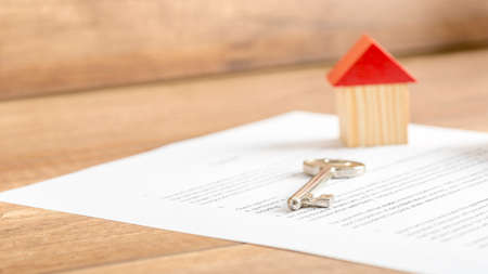 Photo pour Silver house key lying on a contract of house sale, lease, insurance or mortgage in a real estate concept, viewed low angle with focus to the tip. - image libre de droit