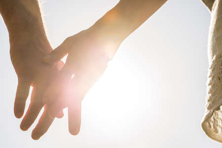 Photo pour Romantic couple with clasped hands backlit by a bright evening sun in a closeup conceptual image of love, commitment and friendship. - image libre de droit