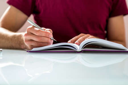 Photo for Close up of a Student Writing Notes or Homework on a Clean Notebook on Top of White Table. - Royalty Free Image