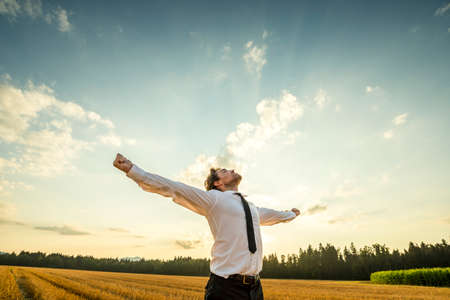 Foto de Half Body Shot of a Thankful Young Businessman Looking up the Sky with Wide Open Arms, Standing at the Open Field. - Imagen libre de derechos