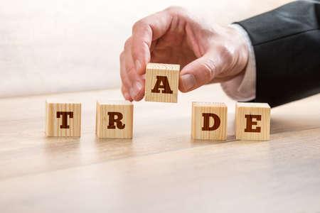 Foto de Closeup of businessman or broker placing a letter A in a line of wooden cubes reading TRADE. Conceptual of finance, investment and constant stock market variability. - Imagen libre de derechos