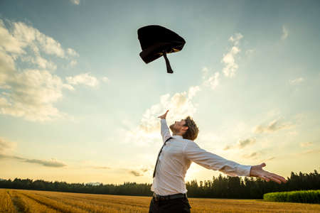 Photo pour Happy Successful Young Businessman Throwing His Coat in the Air for being Free of Something with Wide Open Arms at the Field During Sunset. - image libre de droit