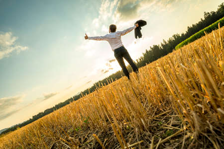 Photo for Rear View of a Successful Young Businessman Standing at the Field with Wide Open Arms and Looking Up in the Sky. - Royalty Free Image