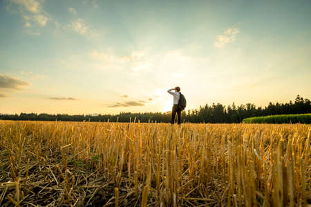 Photo pour Rear View of a Young Businessman Standing at the Field, Looking Into the Distance During Sunset Time. - image libre de droit