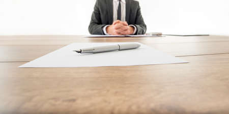 Photo for Businessman sitting at his wooden office desk with contract infront of him and another contract opposite to him with a pen waiting to be signed by employee or business partner. - Royalty Free Image