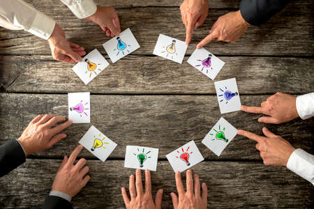 Photo pour Teamwork and brainstorming concept with businessmen seated around a table each pointing to cards with colorful sketches of light bulbs conceptual of bright ideas and solutions arranged in a circle. - image libre de droit