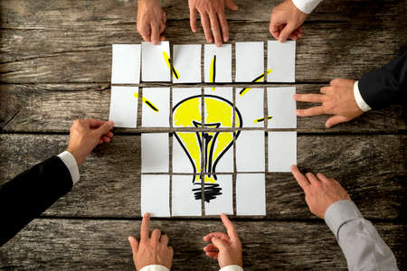 Foto de High angle view of businessmen hands touching white papers arranged on a rustic wooden table forming a yellow light bulb. Conceptual for bright business ideas and innovations. - Imagen libre de derechos