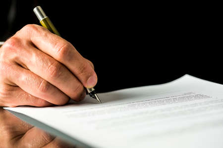 Photo pour Closeup of male hand signing a contract, employment papers, legal document or testament. Isolated over black background. - image libre de droit