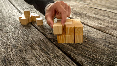Photo pour Closeup of businessman assembling blank wooden cubes into a structured whole on antique wooden desks. Conceptual of business start up, vision and strategy. - image libre de droit