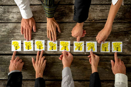 Foto de Brainstorming and teamwork concept with a group of diverse business people each holding out a card with a shining light bulb arranged in a row conceptual of ideas, inspiration and innovation. - Imagen libre de derechos