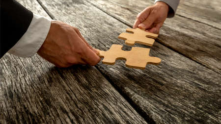 Photo pour Business partnership or teamwork concept with a business people presenting a matching puzzle piece as they cooperate on finding an answer and solution, close up of their hands. - image libre de droit