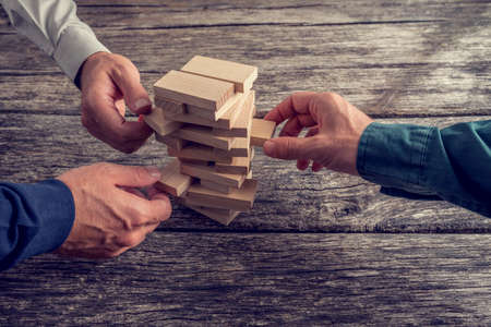 Foto de Three Businessmen Hands Playing Wooden Tower Game on Top of a Rustic Wooden Table. Conceptual of Teamwork, Strategy and Vision. - Imagen libre de derechos