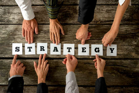 Photo pour Top view of eight business people assembling the word STRATEGY while each holding one card with letter on it. Conceptual of cooperation in finding the best approach to develop business and company. - image libre de droit