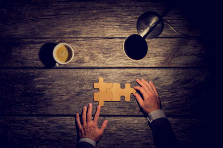Photo pour Overhead view of businessman working late at night at his rustic desk to have finally came to a conclusion or solution about the future of his business by assembling two matching puzzle pieces. - image libre de droit