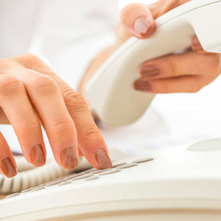 Photo pour Closeup of female telephone operator dialing a phone number making an important business call on white telephone. - image libre de droit