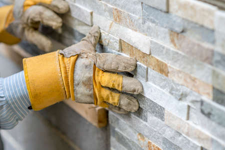 Foto de Closeup of manual worker in protection gloves pushing the tile into the cement on the wall while tiling a wall with ornamental tiles l in a DIY, renovation or construction concept. - Imagen libre de derechos