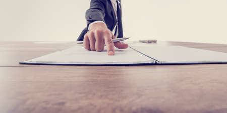 Photo for Front view of employer pointing to a contract where to sign, vintage effect toned image. - Royalty Free Image