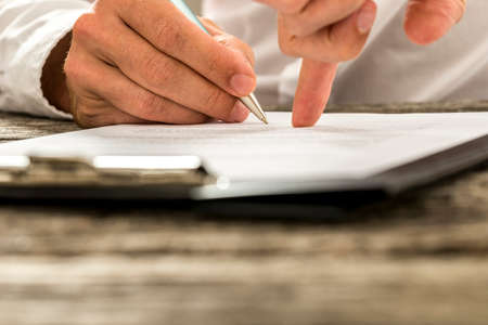 Photo for Closeup of male hand pointing where to sign a contract, legal papers or application form. - Royalty Free Image