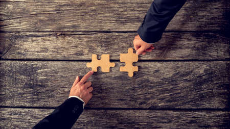 Foto de Retro style image of two business partners each placing one matching piece of puzzle on a textured wooden table. Conceptual of cooperation, innovation and success. - Imagen libre de derechos