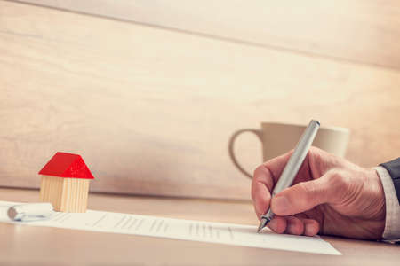 Foto de Closeup of male hand signing insurance papers, contract of house sale or mortgage documents with fountain pen, wooden toy house sitting on paperwork. - Imagen libre de derechos