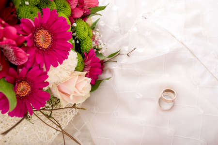 Photo pour Wedding setting - top view of bride and groom rings and beautiful colourful bouquet of flowers on white wedding gown. - image libre de droit
