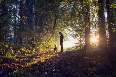 Photo pour Man walking his dog in the woods standing backlit by the rising sun casting a warm glow and long shadows. - image libre de droit