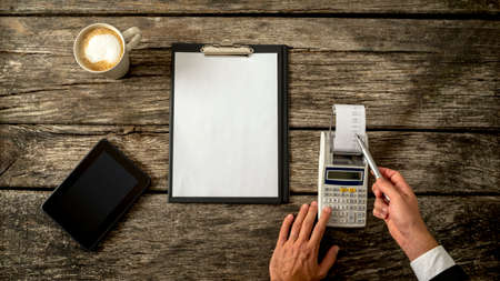 Photo pour Business accountant or financial adviser checking income and expenses in order to write an annual report as he makes calculations on adding machine. With blank sheet of paper in front of him. - image libre de droit
