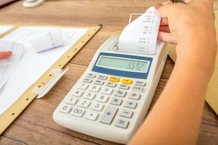 Foto de Tax and accounting concept - female accountant calculating costs and expenses using adding machine checking the receipt and comparing it to paperwork and data. - Imagen libre de derechos