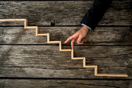 Photo pour Businessman or student walking his fingers up wooden steps resembling a staircase mounted in rustic wooden boards in a conceptual image of personal and career development, success and aspiration. - image libre de droit