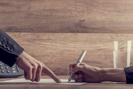 Foto de Closeup of employer showing his employee where to sign a contract, with a retro filter effect. - Imagen libre de derechos