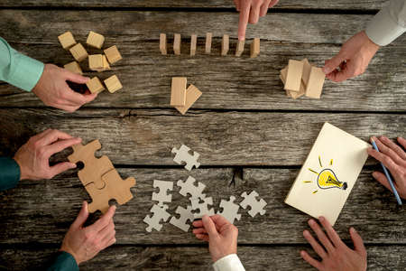 Foto de Businessmen planning business strategy while holding puzzle pieces, creating ideas with light bulb drawn on paper and rearranging wooden blocks. Conceptual of teamwork, strategy, vision or education. - Imagen libre de derechos