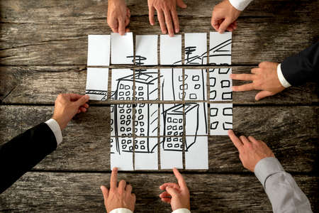 Photo pour Top view of eight architects or urban planners cooperating in urban development and use of land by assembling hand drawn image of high buildings on white cards. - image libre de droit