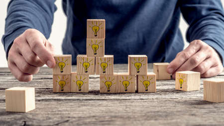 Photo pour Front view of a man arranging wooden blocks with hand drawn yellow lightbulb in a random structure. Conceptual of research, education and innovation. - image libre de droit